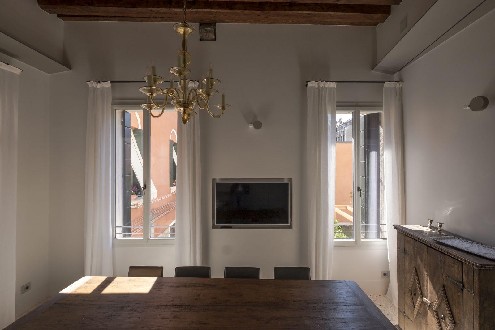 tavolo-cucina-appartamento-zenzero-legno-pregiato-schermo-tv-finestre-lampadario-vetro-murano-venezia-palazzo-morosini