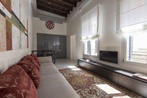soggiorno-appartamento-cayenna-divano-cuscini-lampadario-vetro-murano-televisore-schermo-finestre-luce-tappeto-persiano-venezia-palazzo-morosini