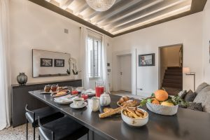 cucina-appartamento-rafano-tavolo-nero-colazione-frutta-succo-marmellata-biscotti-divano-lampadario-soffitto-travi-legno-venezia-palazzo-morosini