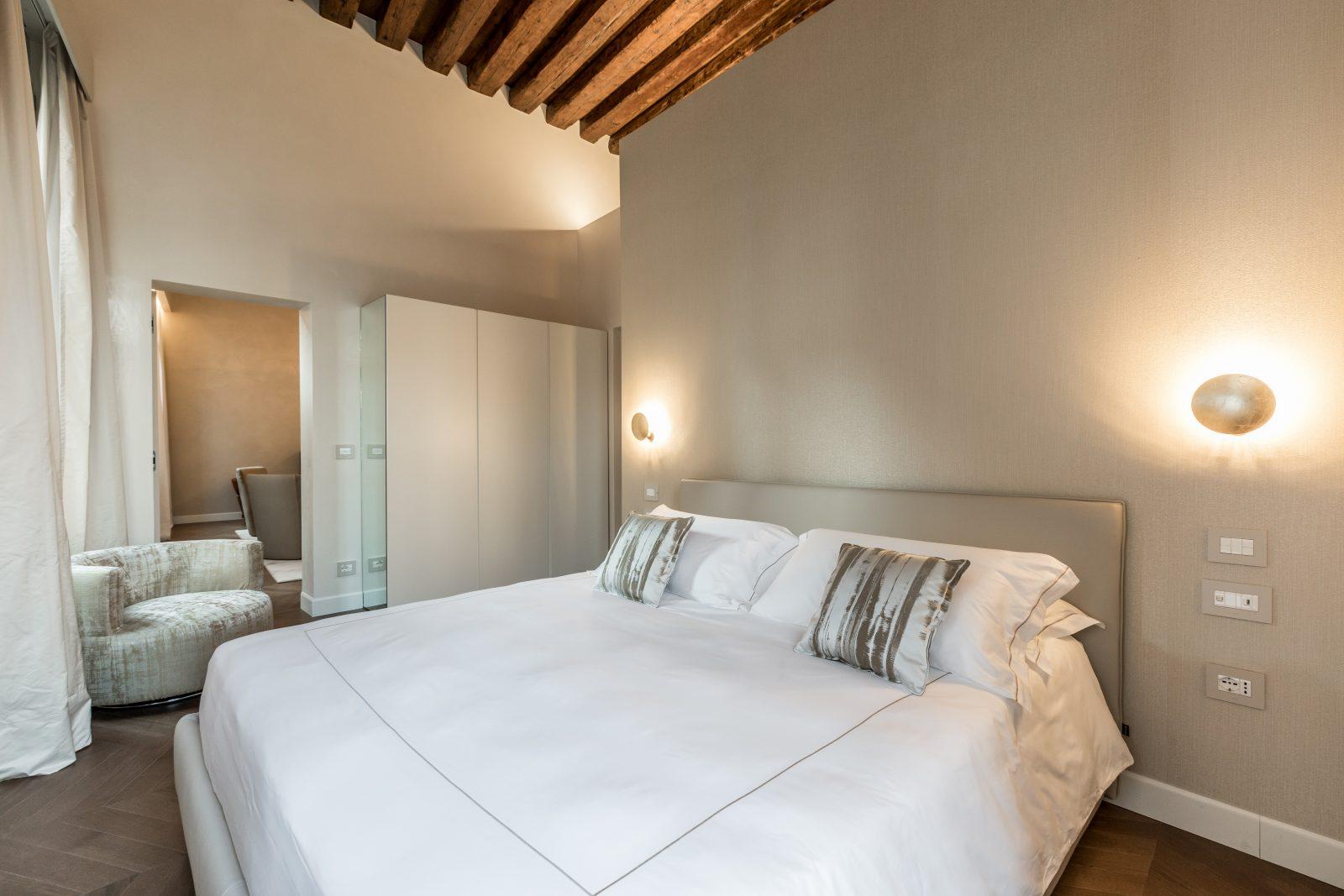 letto-camera-appartamento-zenzero-cuscini-tessuto-lusso-travi-vista-legno-lampade-arredamento-design-venezia-palazzo-morosini