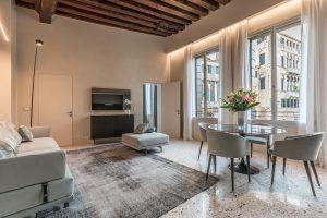 soggiorno-appartamento-coriandolo-finestre-spazioso-luminoso-design-interni-travi-legno-luce-relax-salotto